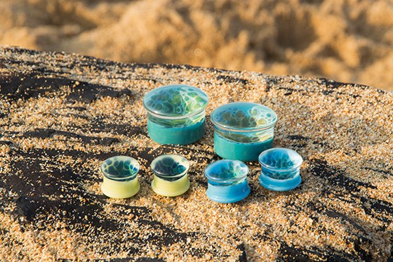 Glass or plastic plugs of various sizes with a blue ocean/wave design, sitting on a sandy wooden bench on the Sunshine Coast