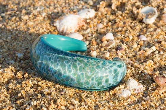 Turquoise bracelet with a wave/ocean design sitting on a sandy Sunshine Coast beach surrounded by shells.