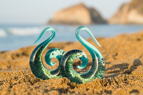 A pair or blue and green ocean/wave design spiral ear stretchers/tapers, sitting on the sand on the Sunshine Coast
